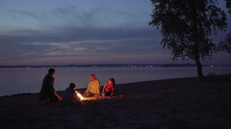 People sit by fire during family hike at beach by sea Стоковые видеозаписи