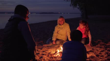 Father stroking son on head by campfire during family hike on beach