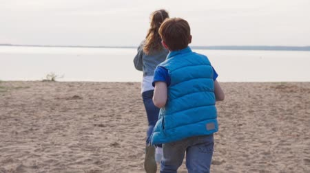 Two children run along sandy beach to seashore