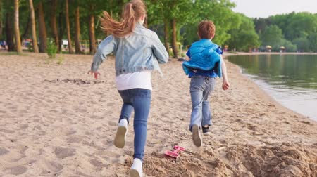 Two kids run along sandy shore