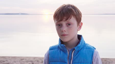 Cute redhead boy with freckles by sea at sunset