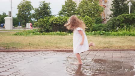 Happy little girl dancing in puddle in white dress in park