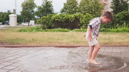 Children having fun and barefoot playing in puddle after rain in park Стоковые видеозаписи