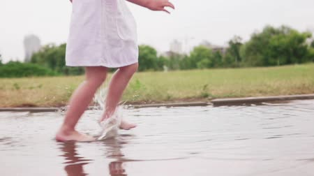 Little barefoot girl running through puddles in white dress in city park