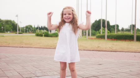 pocsolya : Little joyful barefoot girl jumping in puddle and having fun