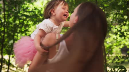 Happy mother hugs adorable little daughter and whirls with her in sunny park
