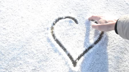 çizmek : Closeup of drawing a heart shape with a finger on fresh winter snow covering pavement high key video