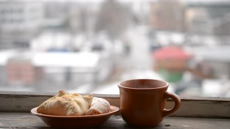 into focus : Earthenware light brown cup with hot drink steaming and buns on saucer on the sill of a balcony on the background of a road with cars moving by and snowflakes falling in winter. Coming into focus. Stock Footage