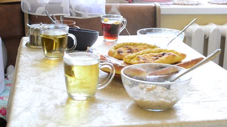 tea bag : Table served with breakfast meal in the kitchen with steam coming out of cups with tea, oatmeal porridge in bowls and appetizing buns in the middle of the table