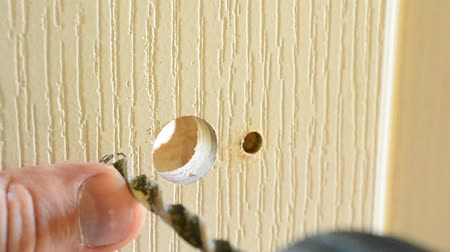 locksmith : Close-up of carpenter hands drilling hole in a white door to install door lock or handle by using electric drill.