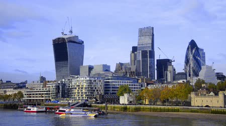 docklands : Boats on Thames river and London skyline, wide angle cityscape lit by the sun on a bright autumn afternoon.