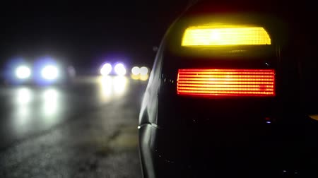 indicador : Flashing orange blinker light on sport car parked on side at night. Traffic passing at background