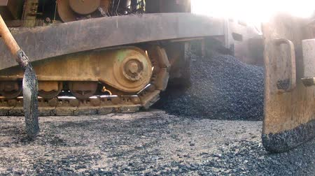 мощение : Clip of heavy equipment asphalt laying machine dropping blacktop tar onto new road