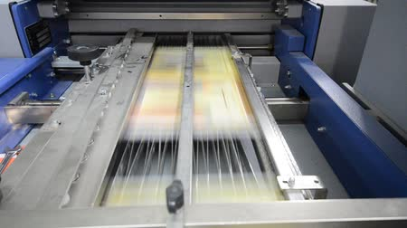 print shop : folding machine folds printed offset sheet as part of newspaper brochure in print house