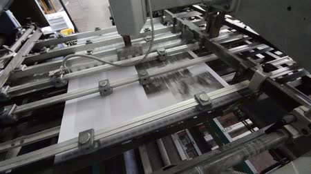 print shop : folding machine HD CRANE SHOOT folds printed offset sheet as part of newspaper brochure in print house Stock Footage