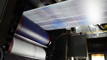 print shop : Web Offset Press Printing Today's Newspaper, Large web offset printing press running at high speed printing a daily newspaper.