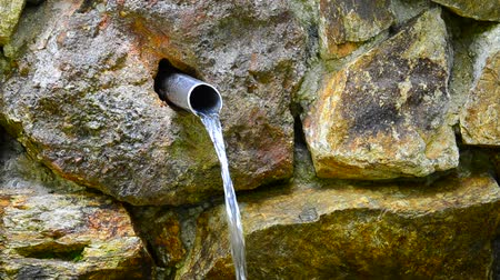 water jet : HD1080i: Jet of ecological clean drinkable water is coming out of a pipe in mountain spring.