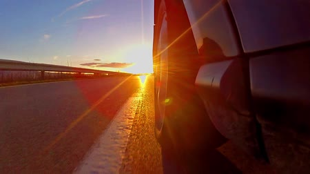 Timelapse of sport car driving down narrow road toward sun rays at sunset, sunrise.