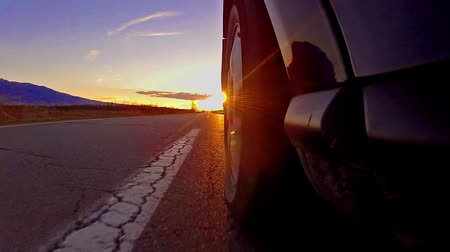 Black sport car in motion by the road. View from on-board camera on weel and wing at sunset, sunrise sun rays, timelapse Stock Footage
