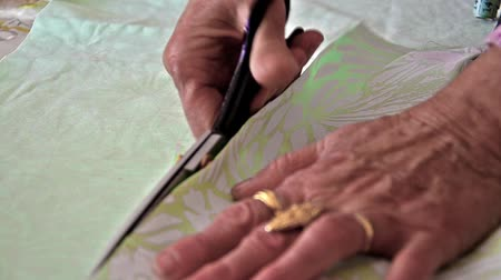 clothing : old lady tailor is cutting with scissors material for wedding clothing industry