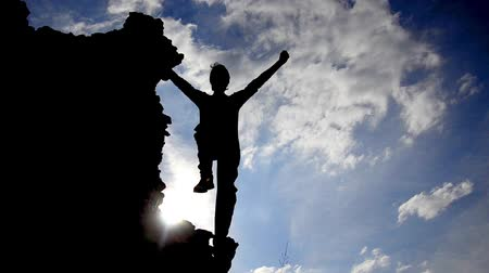 peak : Success Victory Pose by Man on Top of Hill Lifting Hands toward Sun Ray Color Background silhouette