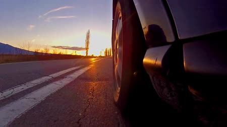 tekerlekler : Black sport car in motion by the road. View from on-board camera on weel and wing at sunset, sunrise sun rays, timelapse Stok Video