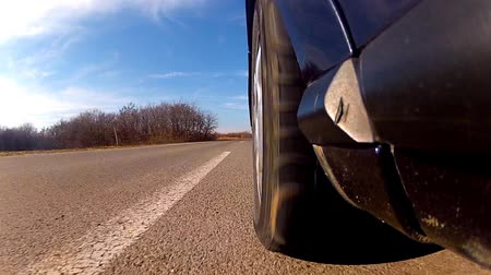 rodas : Sport car rides race fast by a highway road. View from the wheel level. tijmelapse of low angle camera Stock Footage