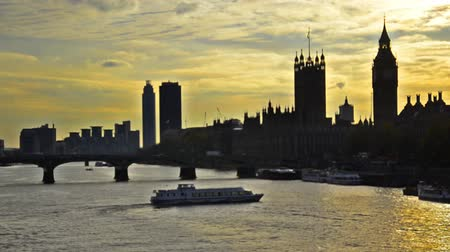 london england : Sunset silhouette of London skyline at sunset, Big Ben and House of Parlament over Westminiister bridge and Thames river. Boats running along the river middle wide shoot