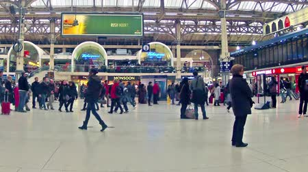 hora : LONDON, UNITED KINGDOM Time table view timelapse panning of Commuters inside Victoria Railway Station