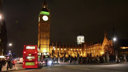 london england : Public bus and other traffic drives past Big Ben in London at night