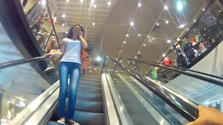 метро : Beautiful girl talking on phone, on escalator stairs at mall
