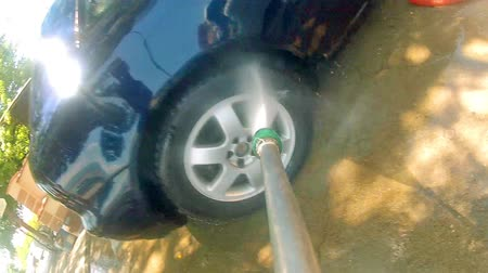 brilhar : Car Pressure Jet Washing POV. Worker washing car. Manual car washing cleaning with foam and pressured water at service station.