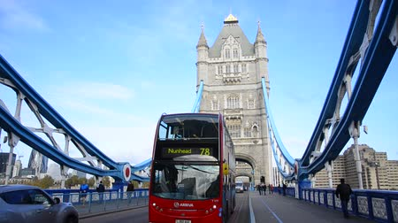 büyük britanya : A london red bus crosses Tower Bridge. Tower Bridge and red buses are iconic symbols of London Stok Video