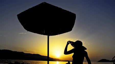 релаксация : TRAVEL CONCEPT of Summer beach sunset with hat girl and straw umbrella silhouette