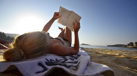 pozisyon : Young women reading a book at the beach with waves in the background, wide shoot