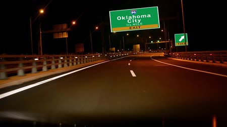city limits : Driving on Highwayinterstate at night,  Exit sign of the Oklahoma Ciry, Oklahoma Stock Footage