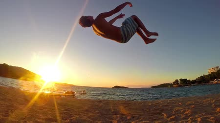 gimnastyka : teen doing gymnastics back flip on the sunset beach in slow motion