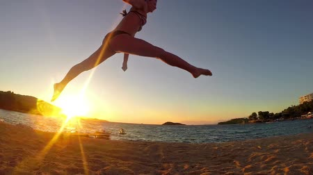 esneme : a young woman with a slender figure is engaged in gymnastics at sea at sunrise silhouette, SLOW MOTION