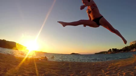 gimnastyka : a young woman with a slender figure is engaged in gymnastics at sea at sunrise silhouette, SLOW MOTION