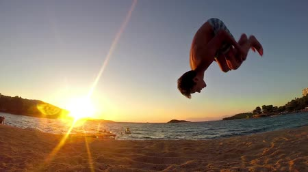 gimnastyka : teen doing gymnastics cartwheels and flip on the sunset beach in slow motion