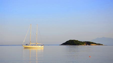 düzgün : Yacht with reflection sails across calm still blue water in the Mediterranean in the Ionian Islands. Stok Video