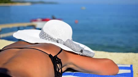 banhos de sol : woman with hat tanning on the beach. summer sunbathing