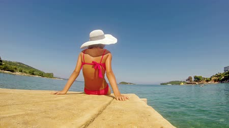 шляпа : 4k, Little Girl with straw hat and bikinni is sunbathing on Sea wodden dock Стоковые видеозаписи