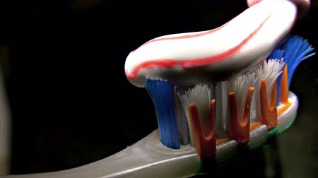 escova de dentes : 4K Detail of toothpaste being squeezed on to a toothbrush on black background. Sony uhd shoot, stock video Vídeos
