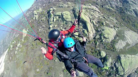 экстремальный : Parasailing, Parascending - Extreme Sports, wide angle shot of two people tandem gliding over rocky mountain Стоковые видеозаписи
