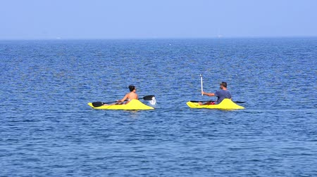 veslování : sea kayak. People having fun rowing at open sea