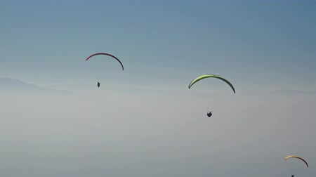 quad hd : Floating in space, paragliders moves smoothly through the air, floating on thermals above the amazing mountain range