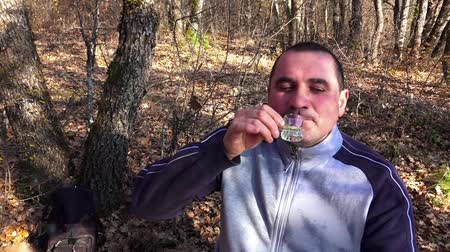 bebida alcoólica : Man drinking whiskey brandy with emotion in forest picnic. Sony 4K steadycam slow motion shot stock video Stock Footage