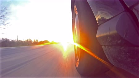 wyprzedaż : UHD Timelapse of sport car driving down narrow road toward sun rays at sunset, sunrise.4K shot