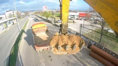 экскаватор : UHD backhoe tractor works on a construction site. Bulldoger worker pov Стоковые видеозаписи